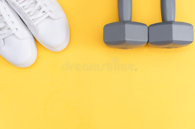 Fitness accessories on a yellow background. Sneakers, bottle of water, earphones and dumbbells stock photos