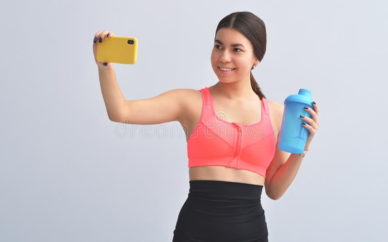 Fitness Apps. Slim Young Girl Using Smartphone During Workout On Yellow Studio Background. Copy Spac. Fitness Apps. Slim Girl Using Smartphone During Workout On royalty free stock image