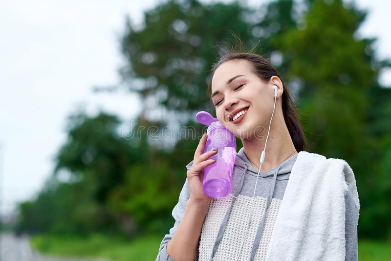 Fitness asian woman with bottle and towel of water after running training in summer park royalty free stock photography