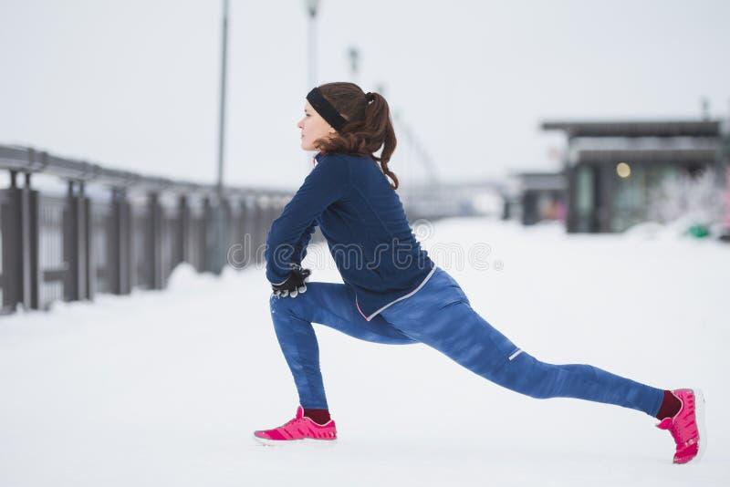 Fitness athlete female model runner doing flexibility exercise for legs before run at snow winter promenade. Telephoto royalty free stock image