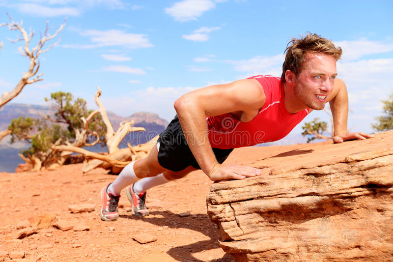 Fitness athlete training push ups in nature. Fitness athlete man training push ups in amazing nature landscape. Strength training fit male working out exercising royalty free stock image