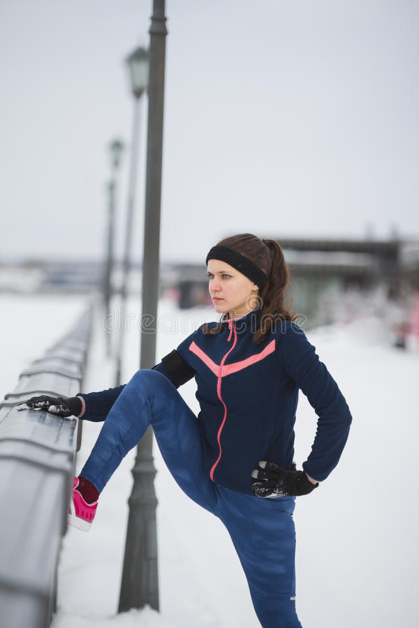 Fitness attractive girl doing stretching outside at snow winter day. Telephoto royalty free stock image
