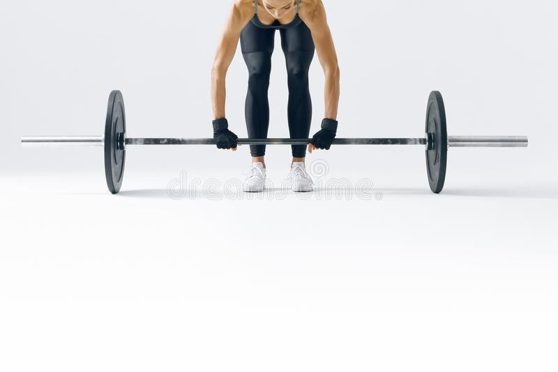 Fit young woman lifting barbell stock photography