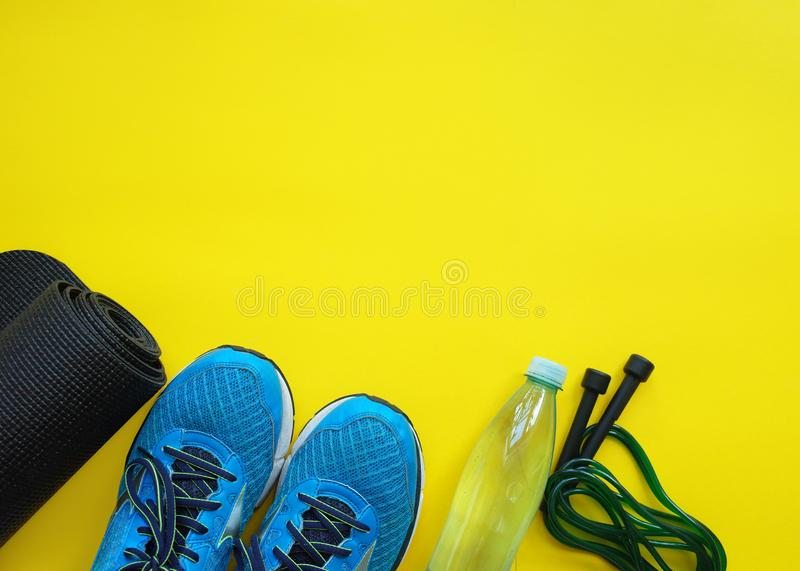 Fitness background. Equipment for gym and home. Jump rope,  mat, water, sneakers  on yellow background top view copy space. royalty free stock photos