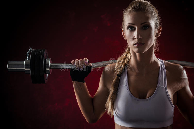 Fitness with barbell. Brutal athletic woman pumping up muscles with barbell on red background stock image