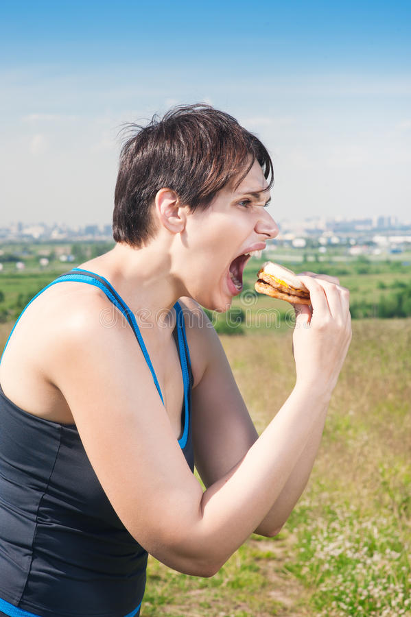 Fitness beautiful plus size woman eating junk food. Outdoor stock image