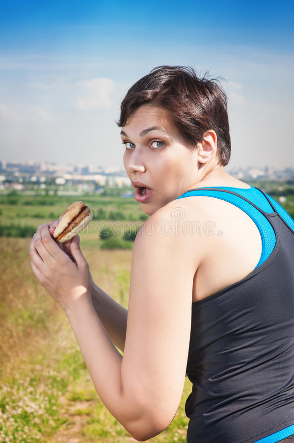 Fitness beautiful plus size woman stealthily eating junk food. Outdoor royalty free stock image