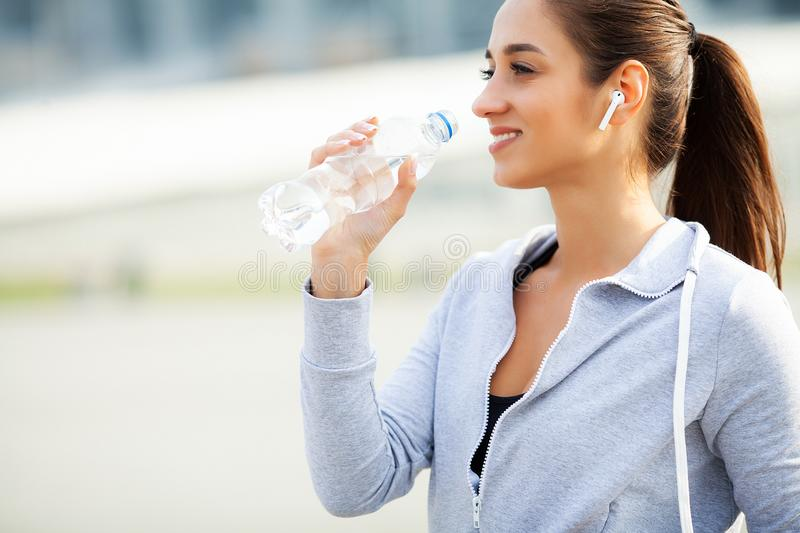 Fitness. Beautiful woman drinking water and listen to music after running stock photography