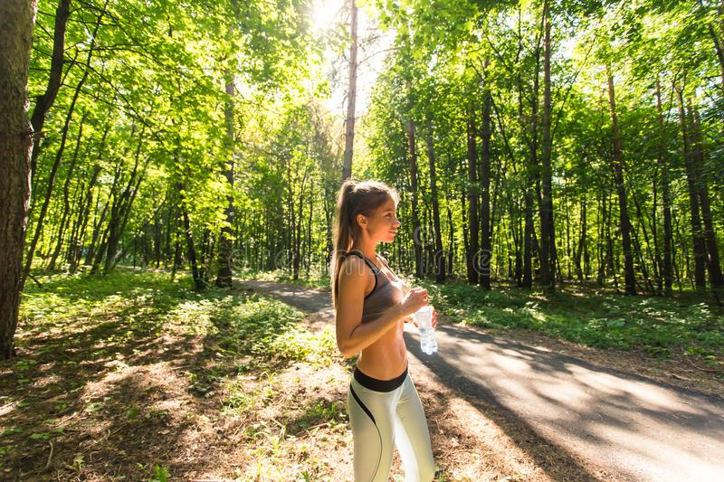 Fitness beautiful woman drinking water and sweating after exercising on summer hot day in park. Female athlete after. Work out royalty free stock image