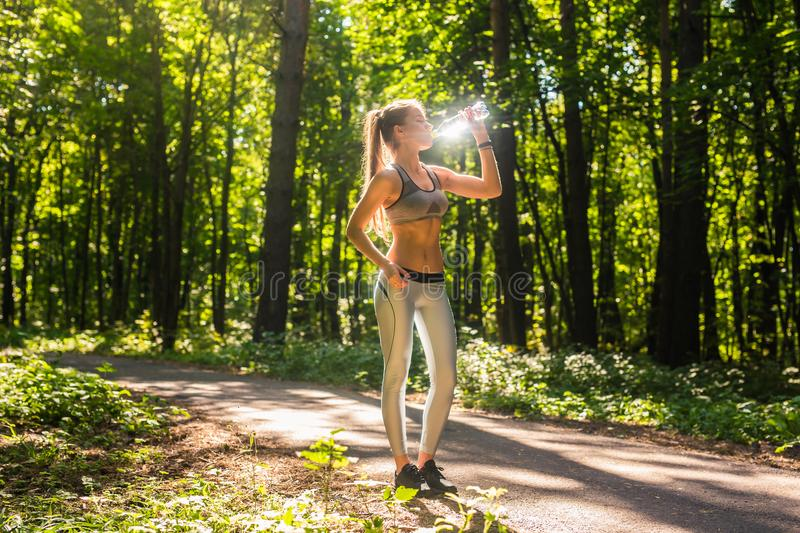 Fitness beautiful woman drinking water and sweating after exercising on summer hot day in park. Female athlete after. Work out royalty free stock photos