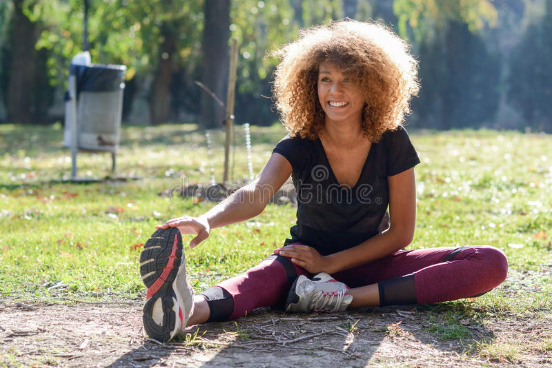 Fitness black woman runner stretching legs after run. Young fitness black woman runner stretching legs after run royalty free stock photo