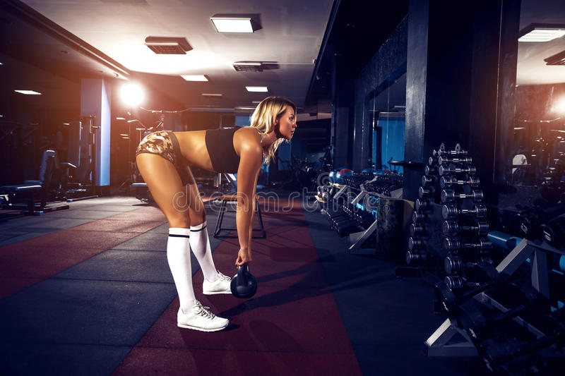 Fitness blonde girl posing and exercising with dumbbell stock photos