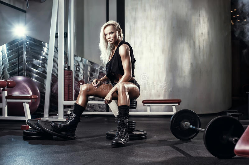 Fitness blonde woman posing on bench in the gym. Fitness blonde girl posing on bench in the gym in military style clothes royalty free stock photo