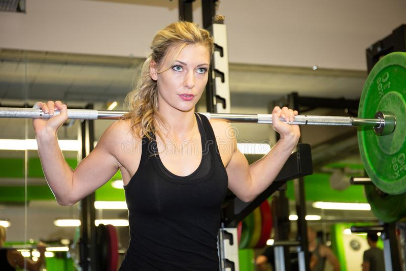 Fitness blonde woman exercising in gym with barbell weights stock photos