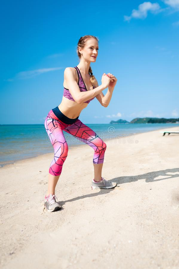 Fitness young woman working out core and glutes with bodyweight workout doing squat exercises on beach royalty free stock photo