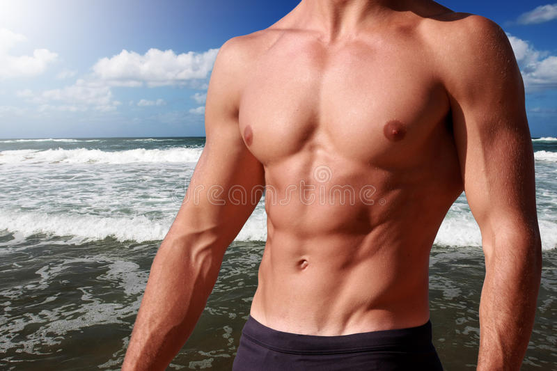 Fitness body abdominal with sea behind. A perfect body with sea behind is exposed to the sun / sea with waves stock photography