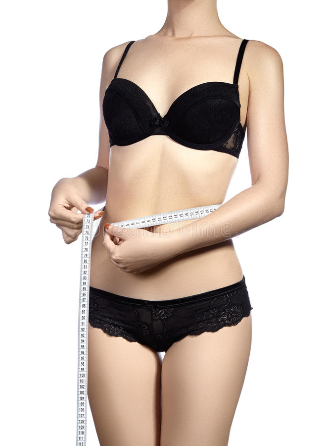 Fitness body with a measurement tape. Beautiful athletic slim woman measuring her waist by measure tape. Siting on diet and with physical exercise. Sexy stock photo