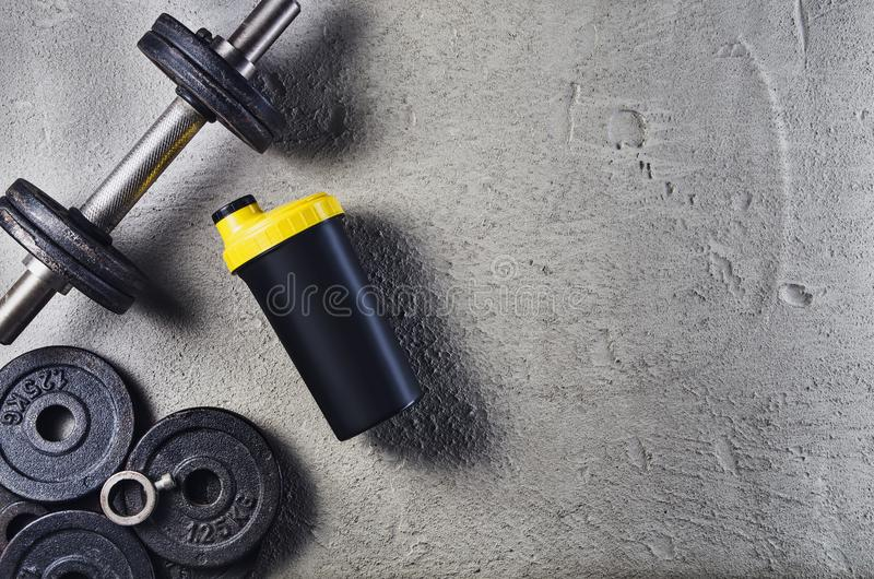 Fitness or bodybuilding background. Dumbbells on gym floor, top view. Fitness or bodybuilding concept background. Product photograph of old iron dumbbells on royalty free stock images