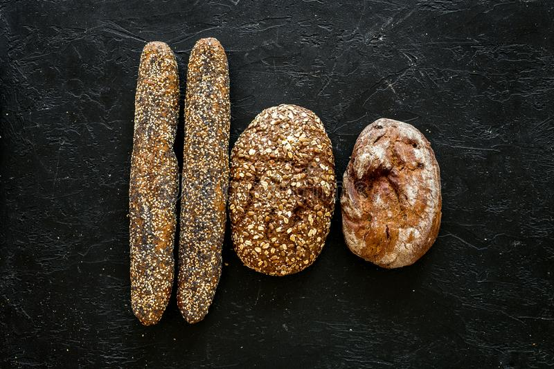 Fitness-bread. Bread made of whole grain flour. Loaf of brown bread and baguette on black background top view copy space. Fitness-bread. Bread made of whole royalty free stock photos