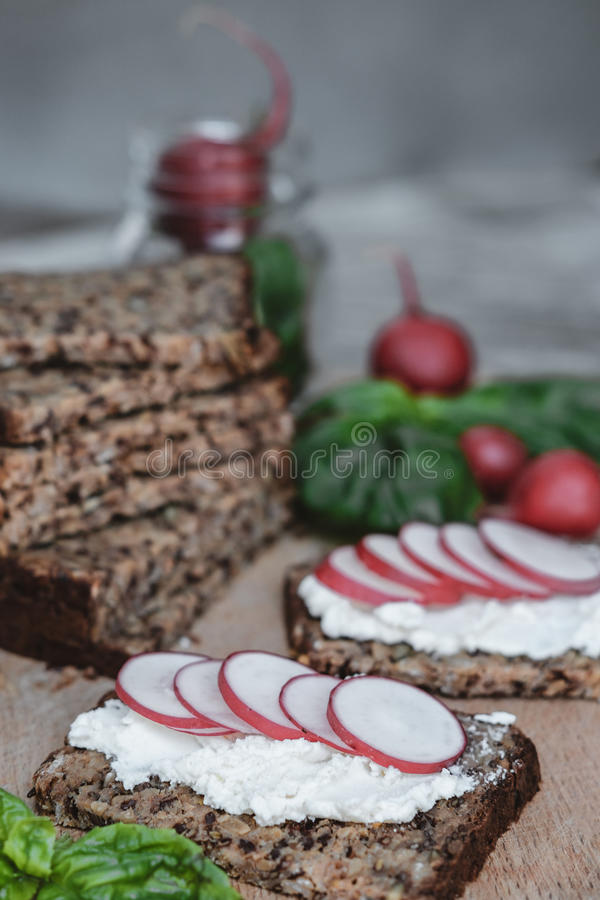 Fitness bread with cottage cheese, radish and basil on rustic wood background, closeup stock photo
