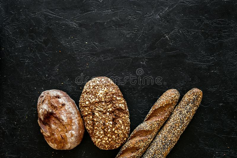 Fitness-bread. Bread made of whole grain flour. Loaf of brown bread and baguette on black background top view copy space. Fitness-bread. Bread made of whole stock photos