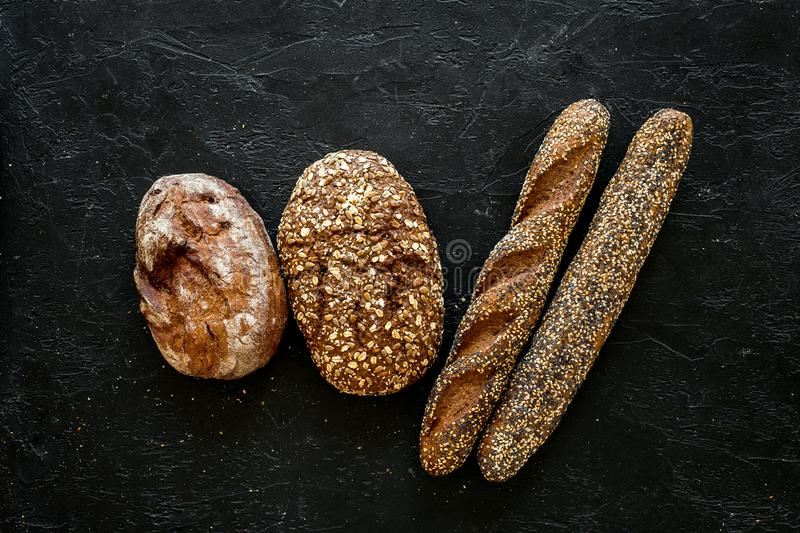 Fitness-bread. Bread made of whole grain flour. Loaf of brown bread and baguette on black background top view copy space. Fitness-bread. Bread made of whole royalty free stock images