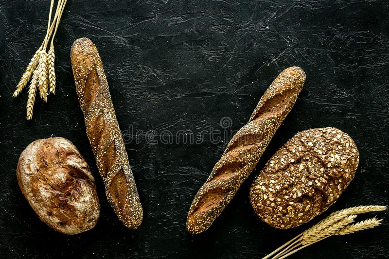 Fitness-bread. Bread made of whole grain flour. Loaf of brown bread and baguette on black background top view space for. Fitness-bread. Bread made of whole grain royalty free stock photo
