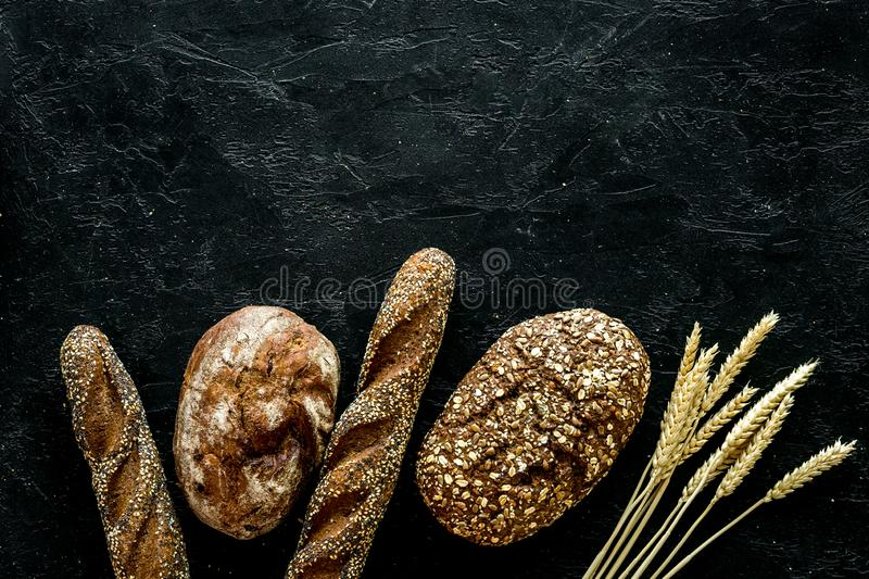Fitness-bread. Bread made of whole grain flour. Loaf of brown bread and baguette on black background top view space for. Fitness-bread. Bread made of whole grain stock image