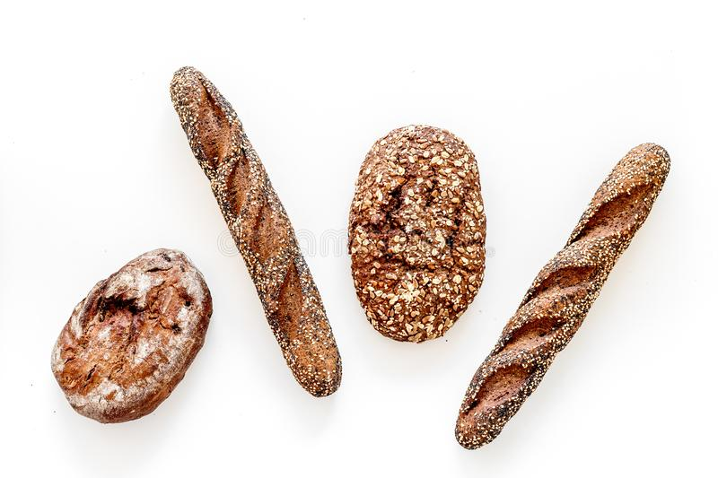 Fitness-bread. Bread made of whole grain flour. Loaf of brown bread and baguette on white background top view.  stock photo
