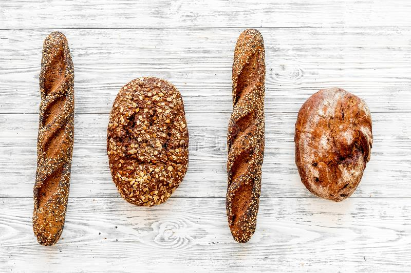 Fitness-bread. Bread made of whole grain flour. Loaf of brown bread and baguette on white wooden background top view.  stock images