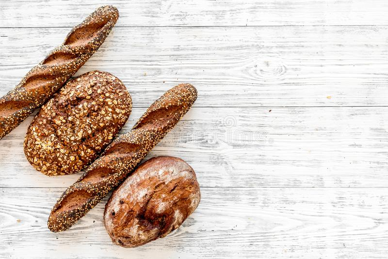 Fitness-bread. Bread made of whole grain flour. Loaf of brown bread and baguette on white wooden background top view.  stock image