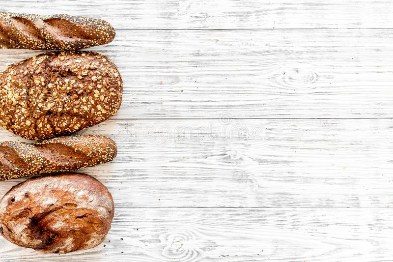 Fitness-bread. Bread made of whole grain flour. Loaf of brown bread and baguette on white wooden background top view.  royalty free stock image