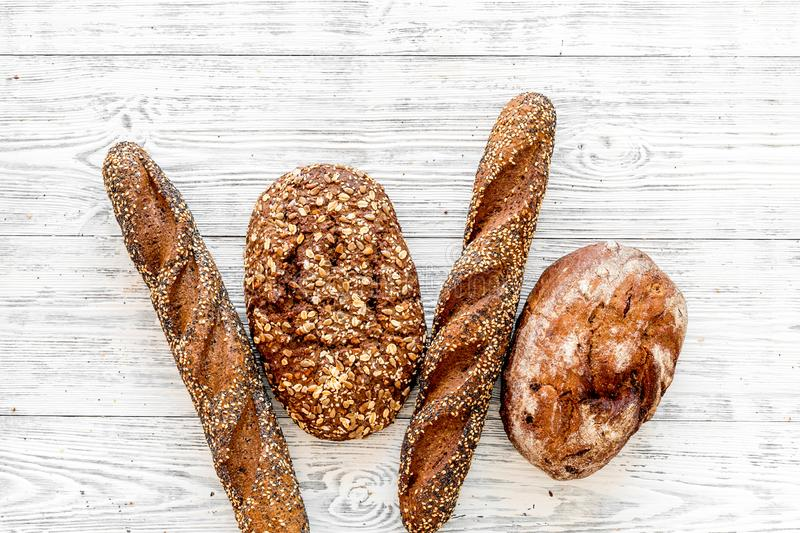 Fitness-bread. Bread made of whole grain flour. Loaf of brown bread and baguette on white wooden background top view.  royalty free stock photography