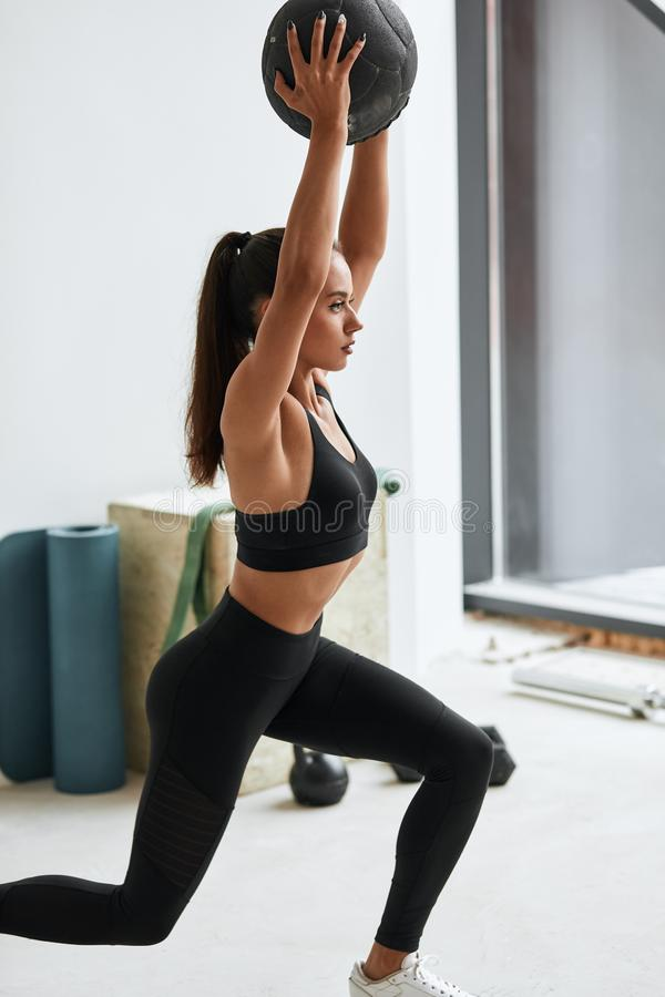 Fit young brunette woman do lunges or squats with ball in gym. Fitness caucasian woman in black topic and leggins do exercises with black fitness ball in gym royalty free stock image