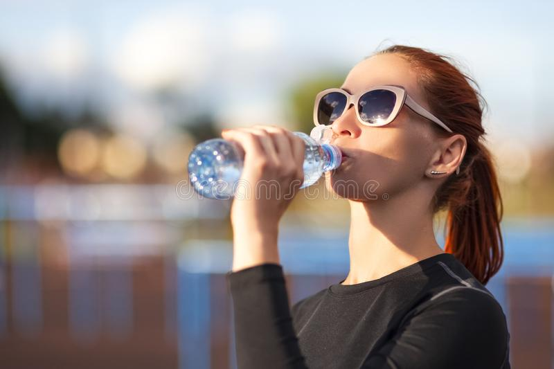 Fitness Caucasian Woman in Sportwear and Sunglasses Drinking Water from Bottle Outdoors royalty free stock photos