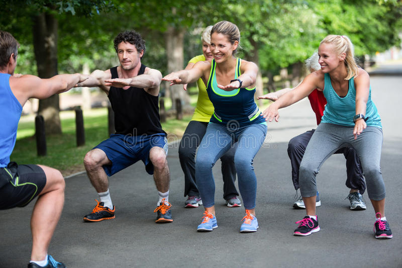 Fitness class doing squat sequence royalty free stock image