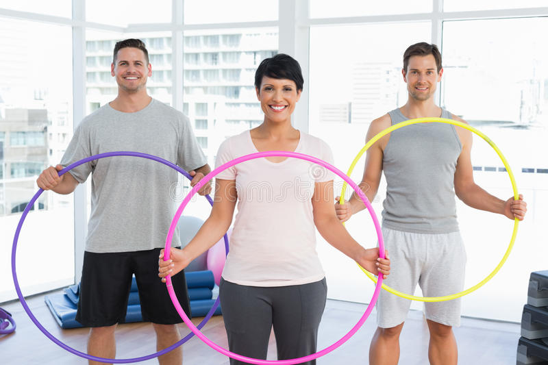 Fitness class holding hula hoops in gym. Portrait of fitness class holding hula hoops in bright gym royalty free stock images