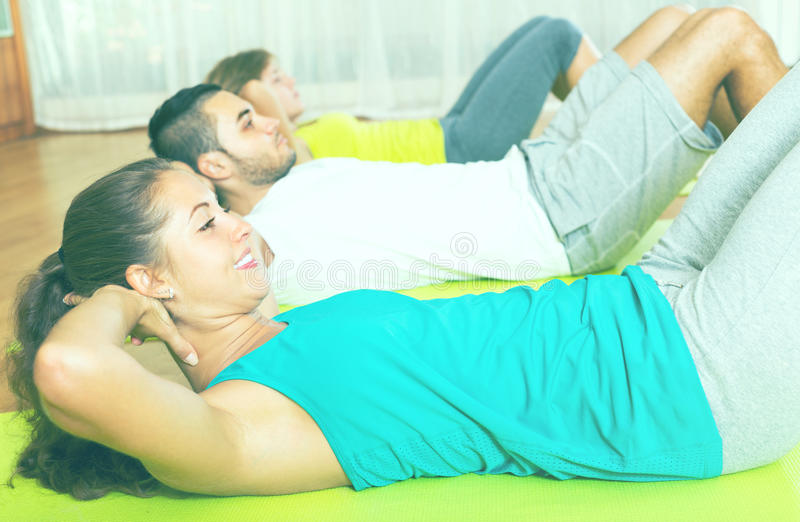 Fitness class in sport club. Group of three doing exercises in sport club. Focus on girl stock photos