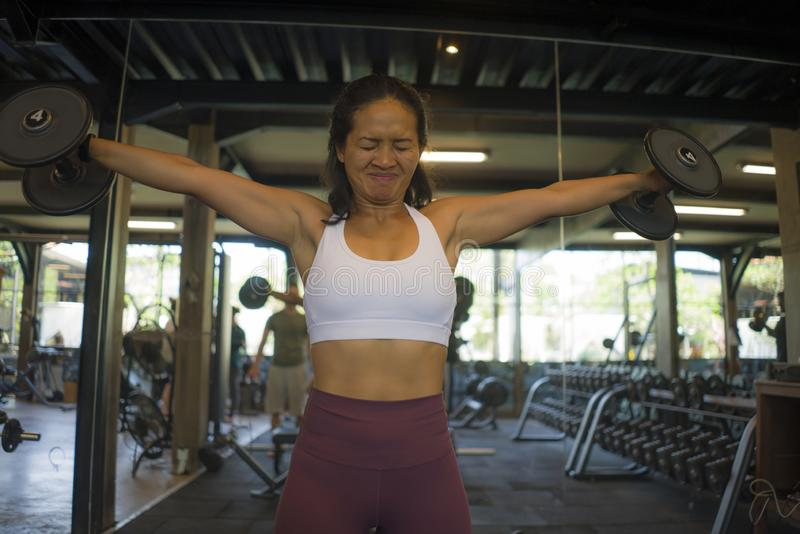 Fitness lifestyle portrait of young attractive and athletic Asian Indonesian woman training hard working out at gym lifting weight stock photos