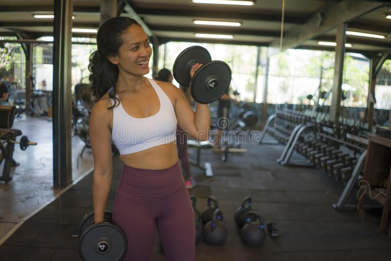 Fitness club lifestyle portrait of young attractive and happy athletic Asian Indonesian woman training hard at gym lifting weight stock photo