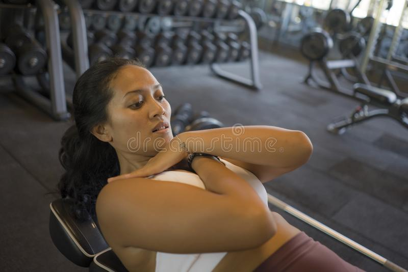 Fitness club portrait of young attractive and determined athletic Asian Indonesian woman training at gym bench doing abdominal stock image