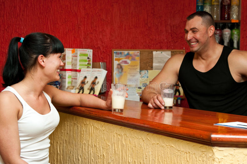 Fitness club reception desk. Instructor talking to a satisfied client at fitness club reception desk, both drinking refreshment drink stock images