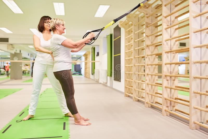 Fitness coach helps with the sling training stock images