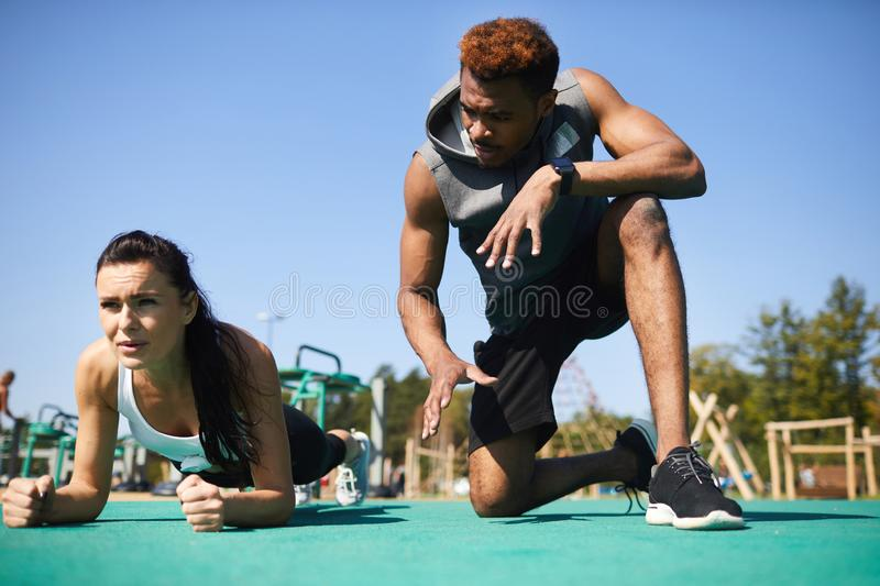 Fitness coach supporting trainee at stadium. Professional black fitness coach gesturing hands while supporting trainee at stadium, frowning young women doing royalty free stock photography
