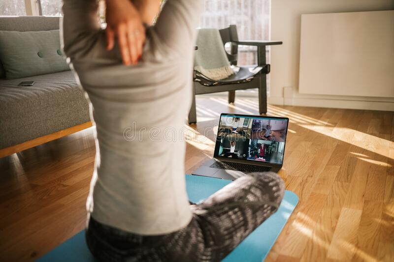 Fitness coach teaching yoga online to group of people. Yoga trainer demonstrating yoga poses to students via video conference stock photography