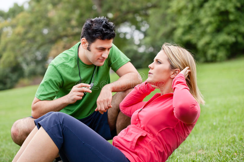 Fitness coach with woman doing sit ups. A fitness coach training women doing sit ups stock images