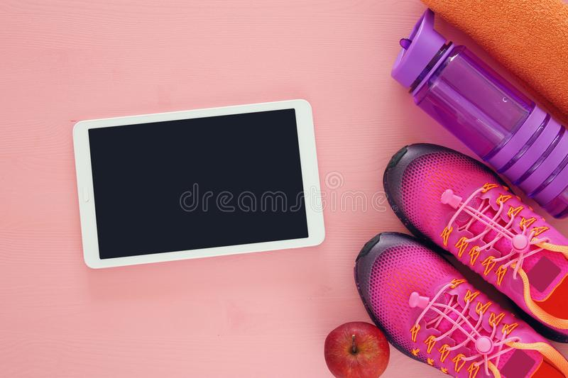 Fitness concept with bottle of water, towel, tablet devise and woman pink sport footwear over colorful background.  stock photography