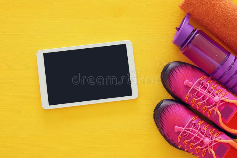 Fitness concept with bottle of water, towel, tablet devise and woman pink sport footwear over colorful background.  royalty free stock photography