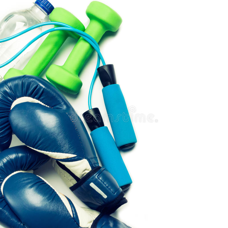 Fitness concept - boxing glove, dumbbells, skipping rope and bottle. On the white background royalty free stock images