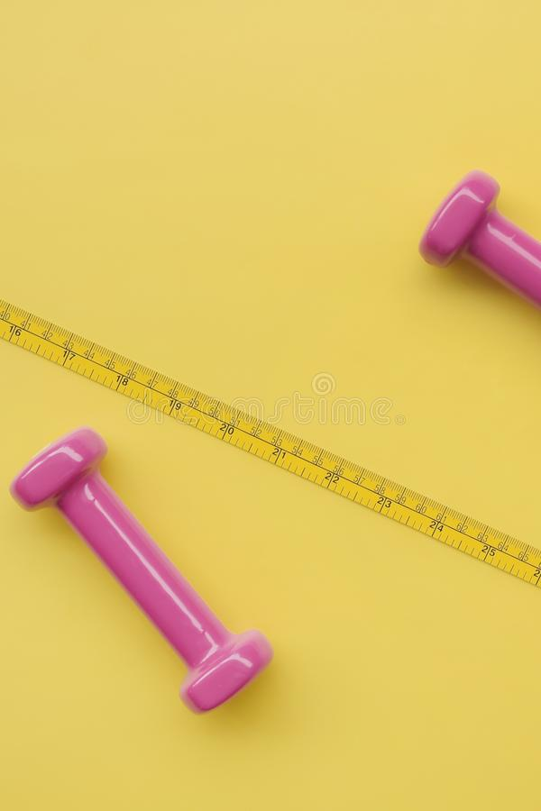 Fitness concept dumbbell and measuring tape. On yellow background stock photography